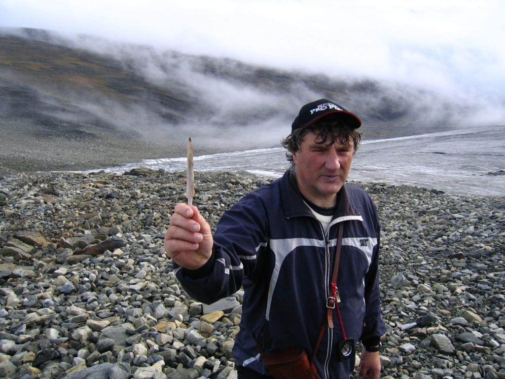 Jan Stokstad holding a bone arrowhead, found during the big melt in 2006.