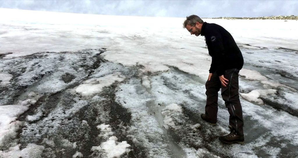 Lars Pilø standing on ancient dark ice, exposed on the surface of on ice patch