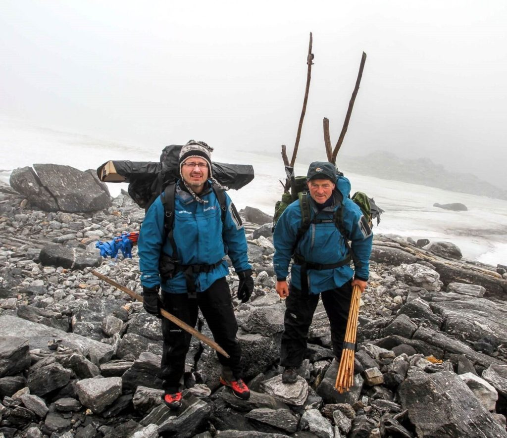 Reidar and Lars in the Lendbreen mountain pass, carrying finds.