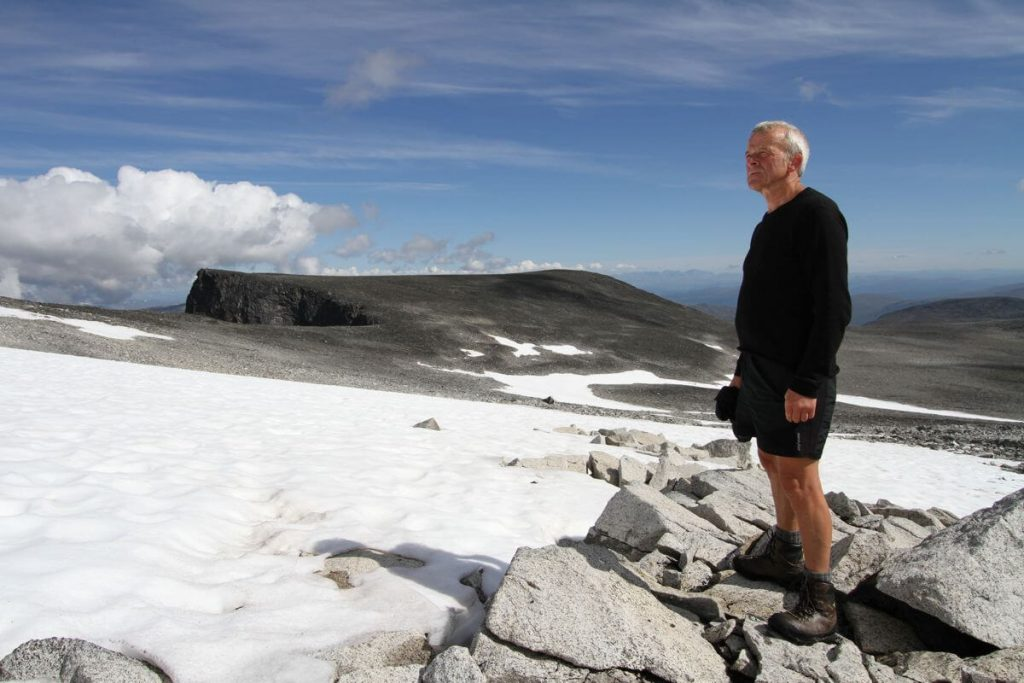 Reidar Marstein standing at the edge of an ice patch in the Jotunheimen Mountains.