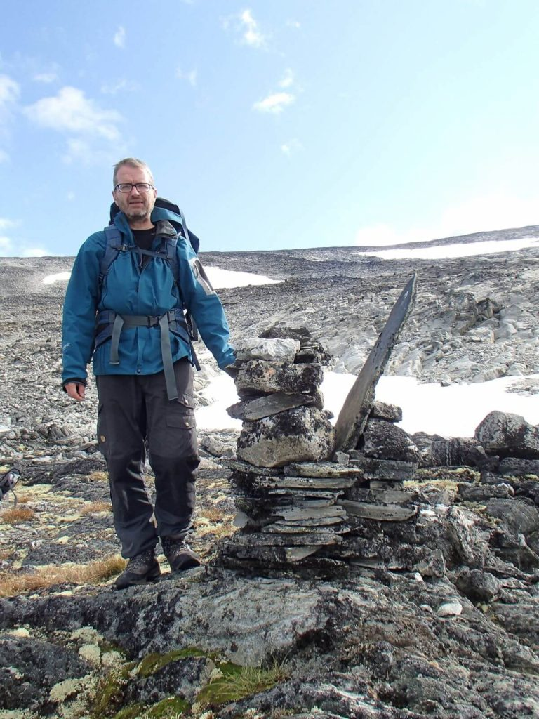A cairn, overgrown with lichen, marking the route over Lendbreen ice patch.